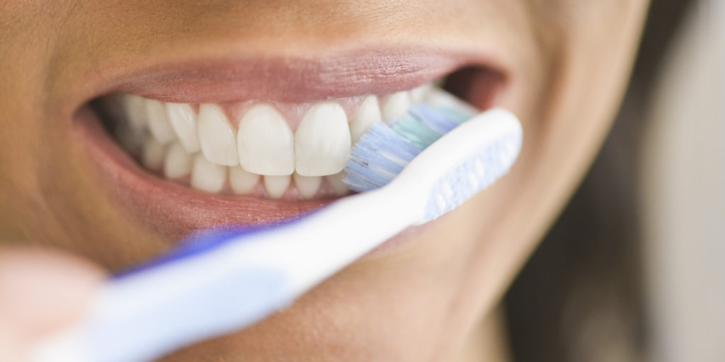 Close up of person brushing teeth often and regularly.